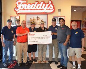 Men holding a large check for a donation from Freddys