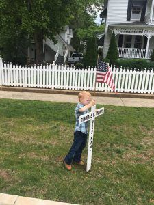 Three year old Issac Sullens placing a flag on a cross