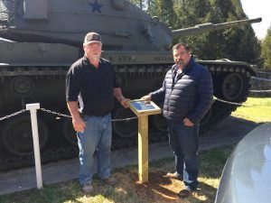 Two men help install a tank display plaque