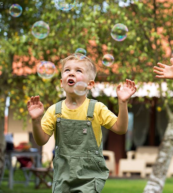 A boy jumping into bubbles in his yard